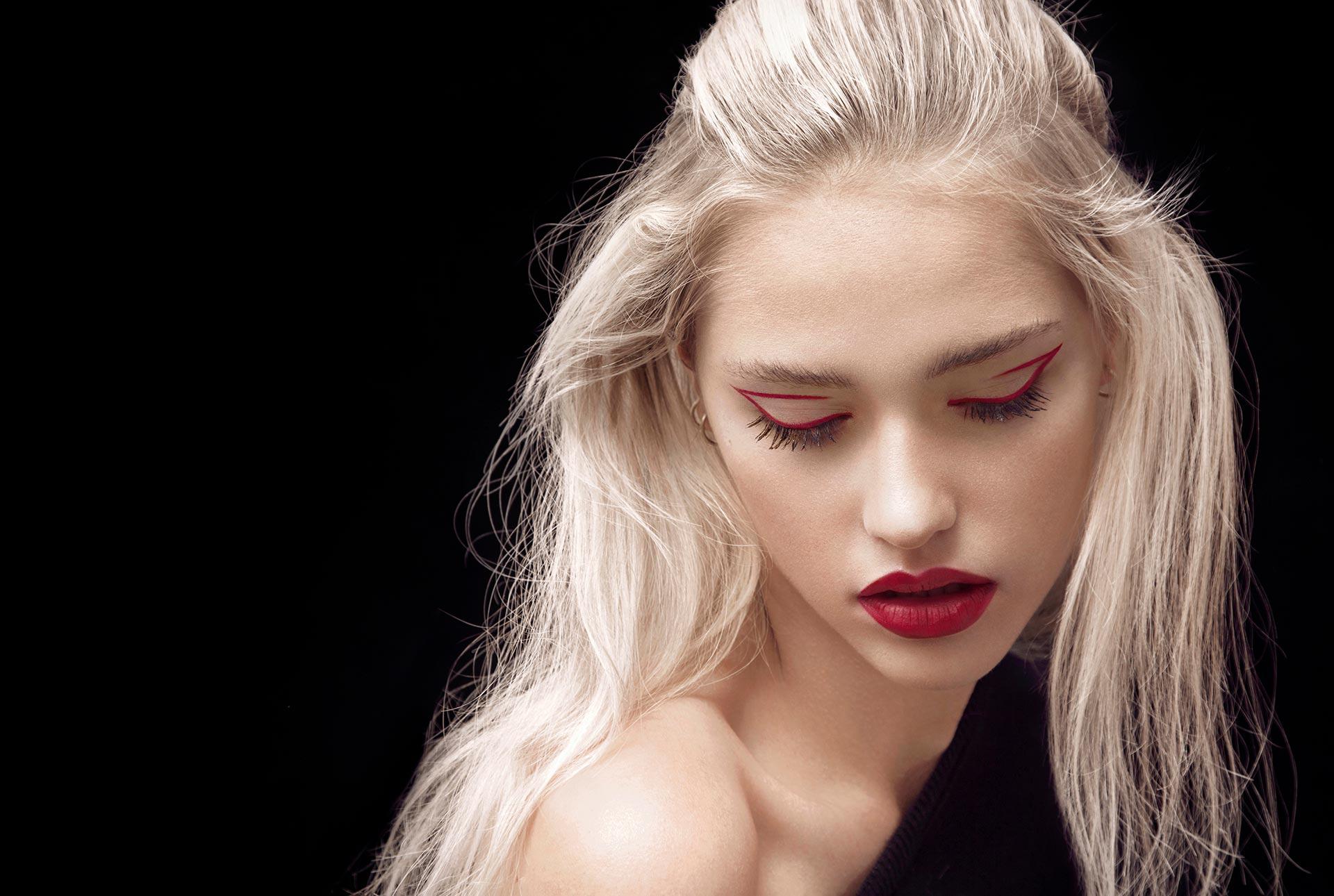Dame blonde portant un fard à paupières rouge et une liste rouge de Chanel