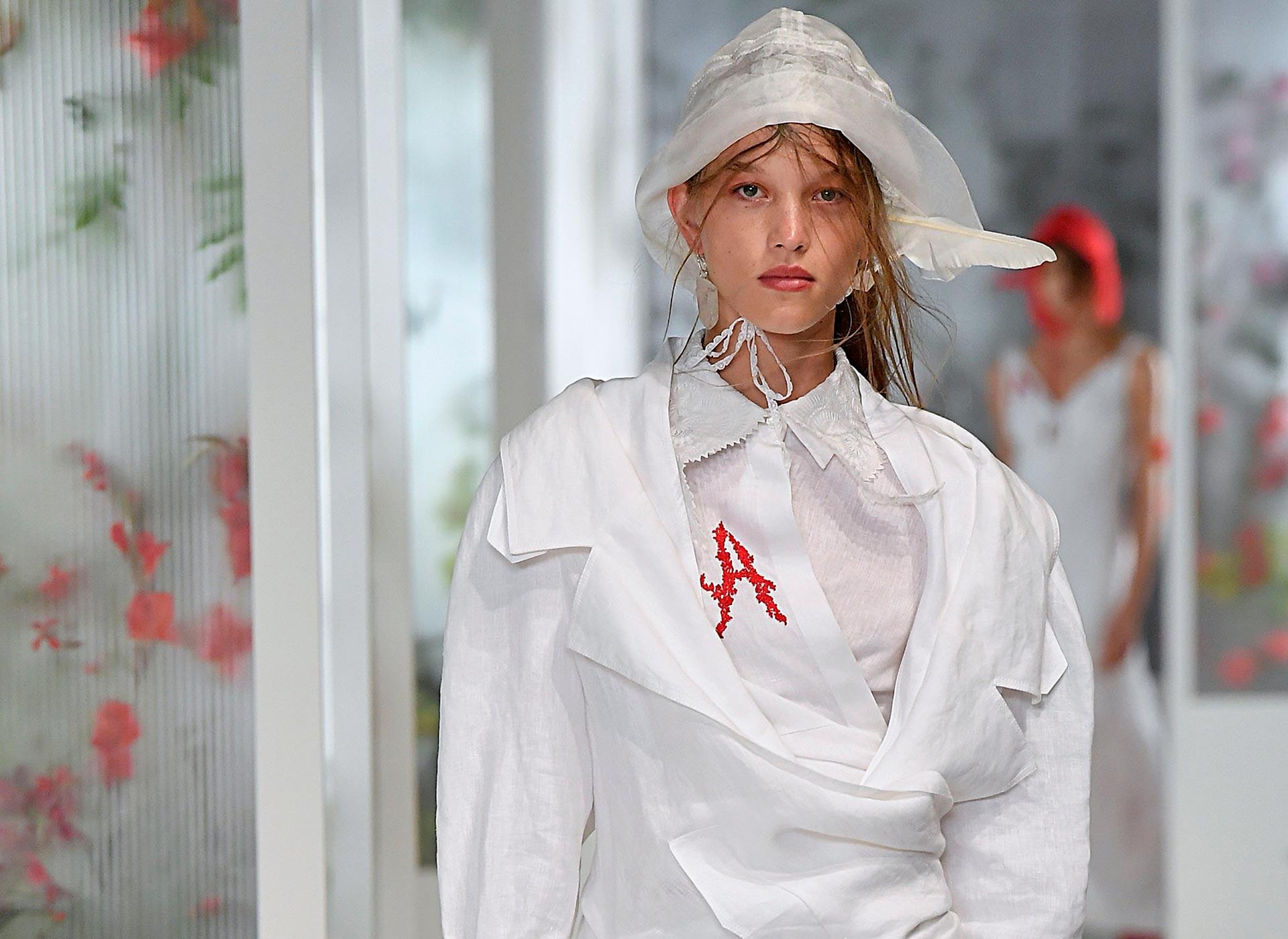 """Dame portant une tenue blanche, par Preen, brodée d'une lettre rouge """"A"""""""