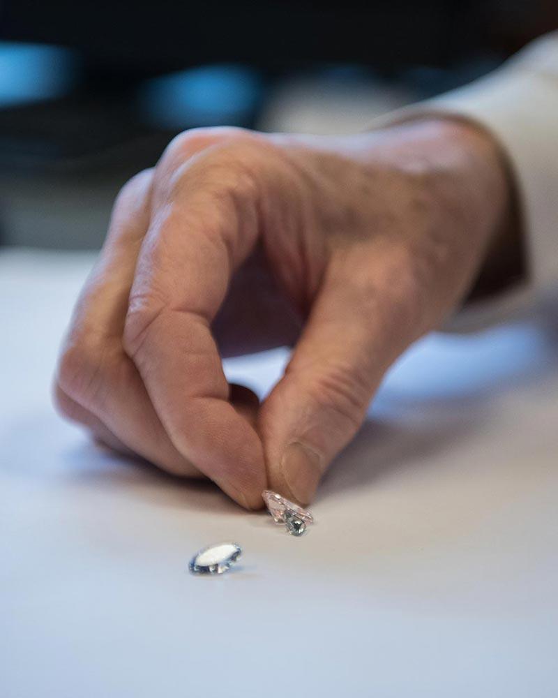 BIJOUTERIE – Gros plan d'une main touchant des diamants.